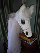 Close up of my Beautiful Dream Horse's head and neck, made using chicken wire, stockings full of Grocery bags and painted with acrylic, sealed with water based lacquer, and wearing her pink taffeta dress, with silver bridle!